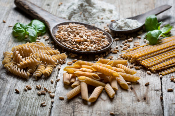 Raw spelt pasta Close-up of raw spelt, flour and dinkel pasta spelt stock pictures, royalty-free photos & images