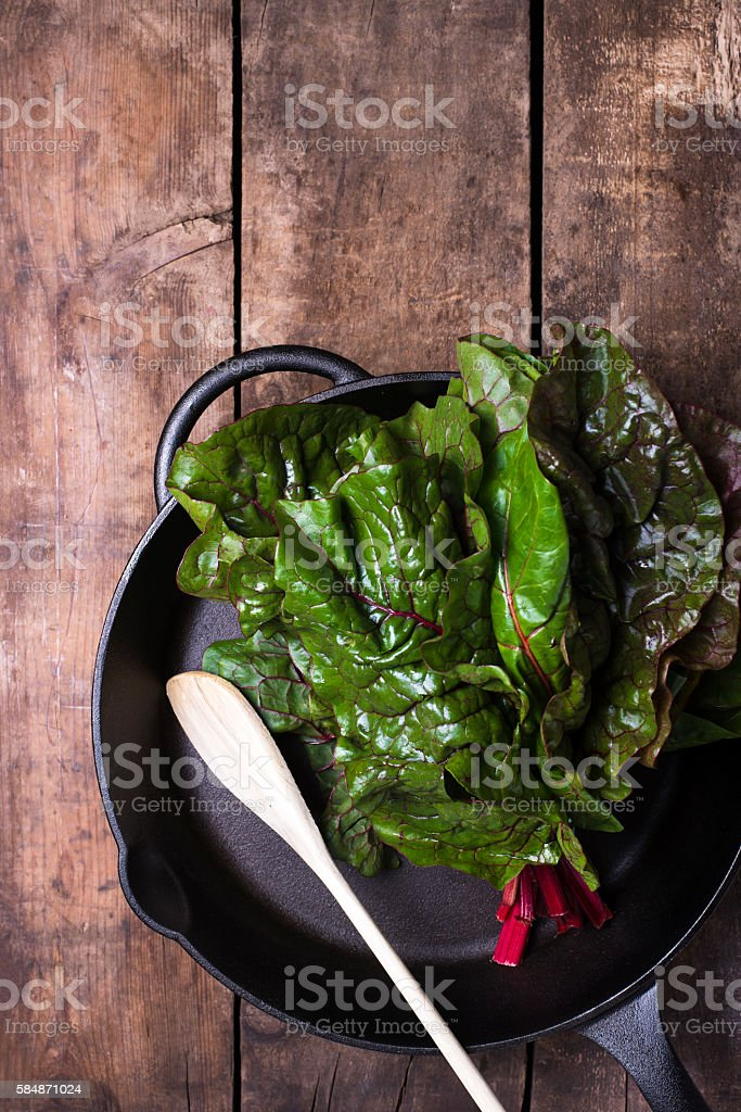 raw spinach in an iron cast skillet - foto de stock