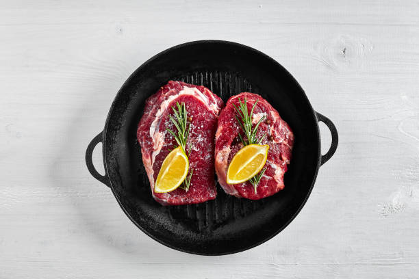 Raw Steak in grill frying pan with herbs and oil on white background, top view, place for text Raw Steak in grill frying pan with herbs and oil on white background, top view, place for text. Copy space. Still life. Flat lay overhead projector stock pictures, royalty-free photos & images