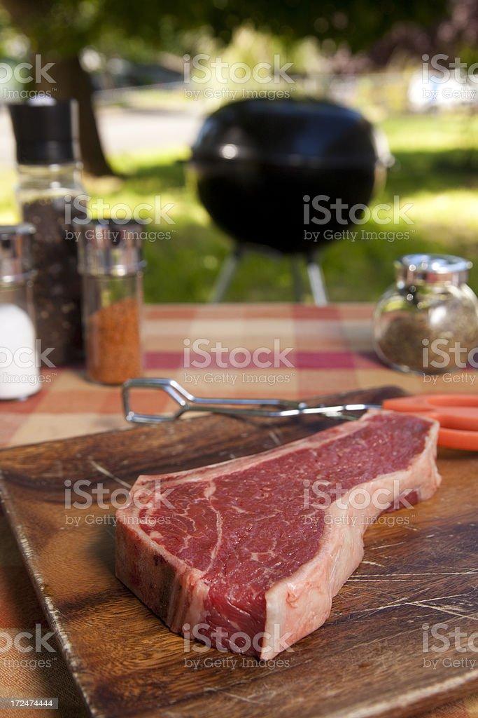 Raw Steak Near A Grill royalty-free stock photo