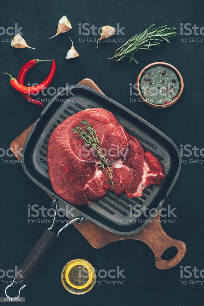 raw steak on grill pan with various spices around stock photo