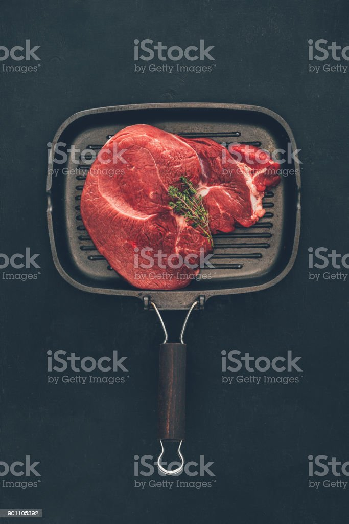 raw steak with herb on grill pan stock photo
