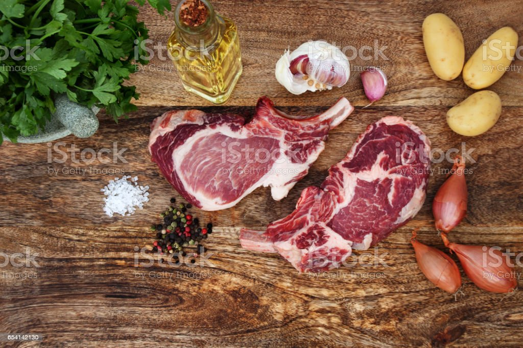 Raw steaks with ingredients for grilling stock photo