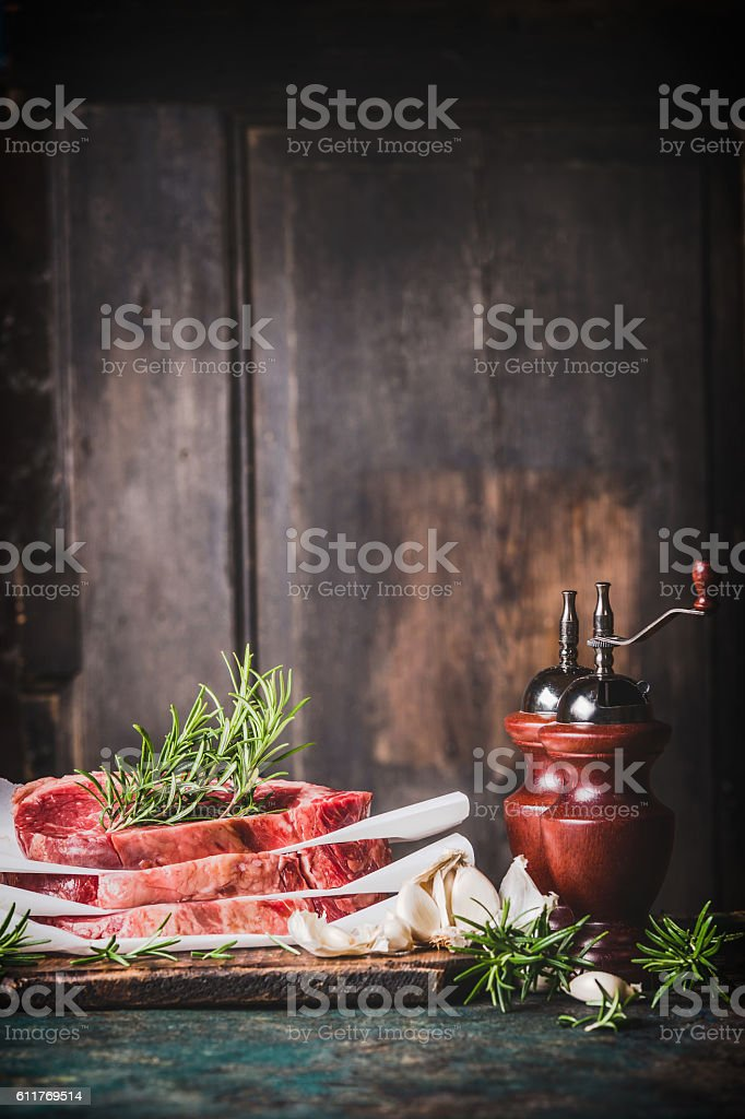Raw steaks with  salt and pepper mills on kitchen table – Foto