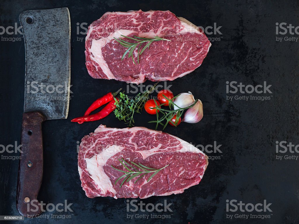 Raw stek with cleaver stock photo