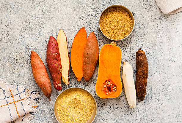 Raw Sweet Potatoes And Butternut Squash On Marble Table stock photo