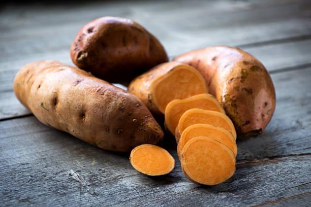 surowe słodkie ziemniaki na drewnianym tle, zbliżenie - słodki ziemniak zdjęcia i obrazy z banku zdjęć