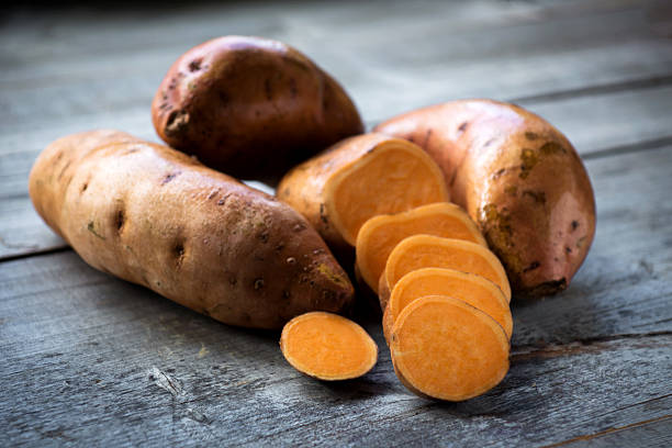 Raw sweet potatoes on wooden background closeup Raw sweet potatoes on wooden background closeup sweet potato stock pictures, royalty-free photos & images
