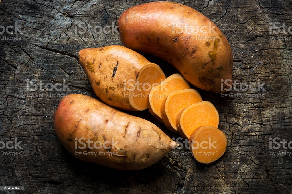 Raw sweet potatoes on wooden background closeup stock photo