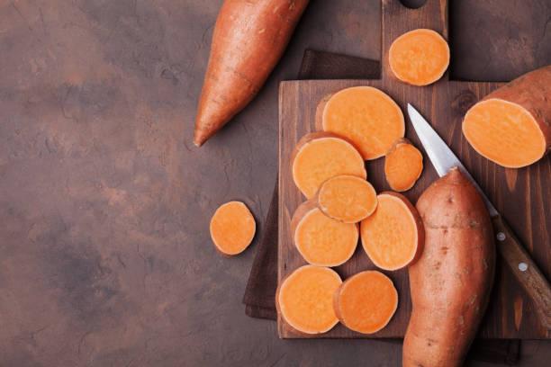 surowe słodkie ziemniaki na drewnianej płycie kuchennej z widokiem z góry. żywność ekologiczna. - słodki ziemniak zdjęcia i obrazy z banku zdjęć