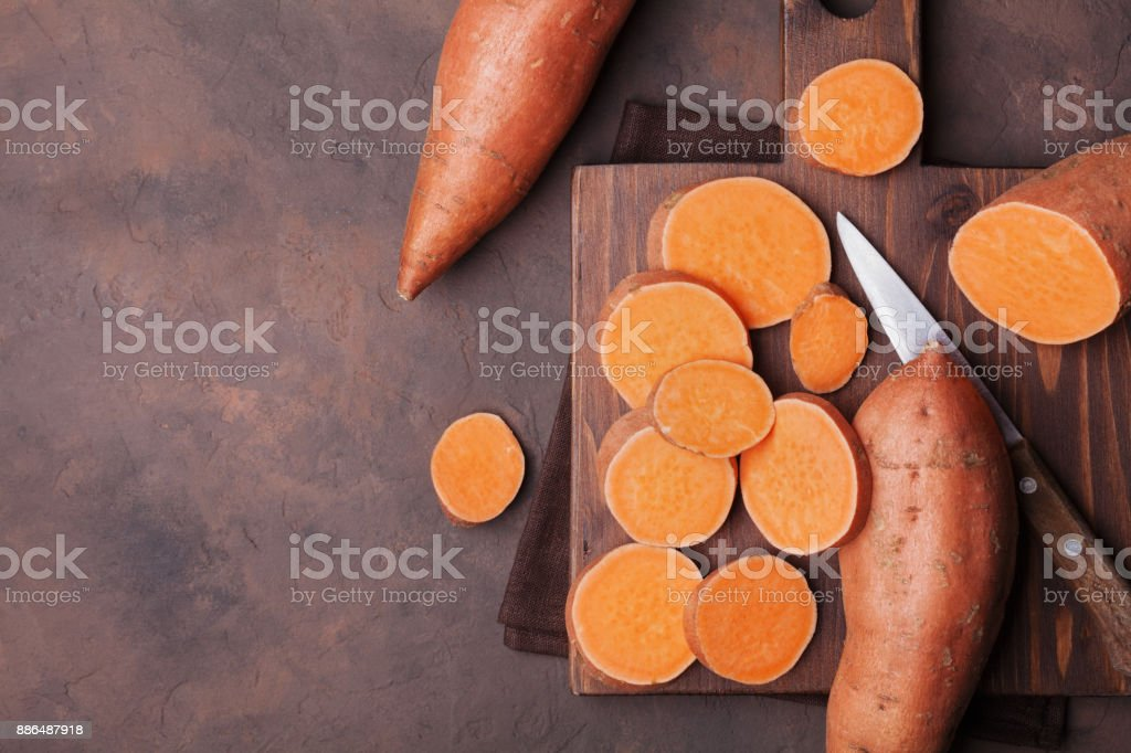 Raw sweet potatoes on wooden kitchen board top view. Organic food. - fotografia de stock