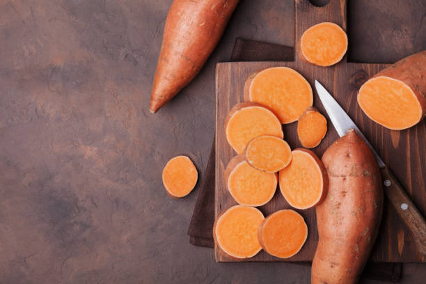 Raw sweet potatoes on wooden kitchen board top view. Organic food. Raw sweet potatoes on wooden kitchen board top view. Organic food. Copy space for text or design. sweet potato stock pictures, royalty-free photos & images