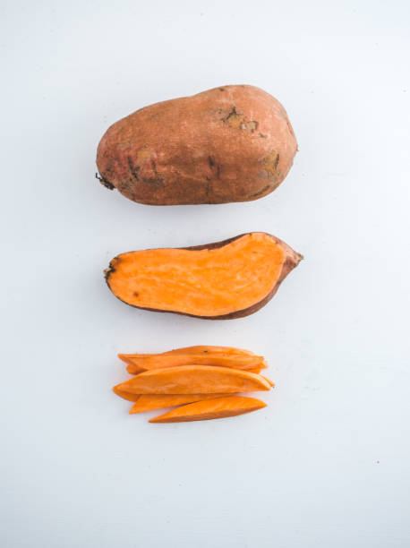 Raw sweet potatoes Whole, half and chopped sweet potatoes isolated on white sweet potato stock pictures, royalty-free photos & images