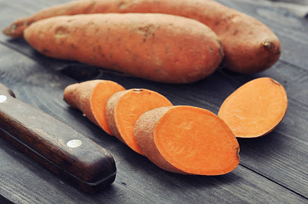 Raw sweet potatoes Raw sweet potatoes on wooden background closeup sweet potato stock pictures, royalty-free photos & images