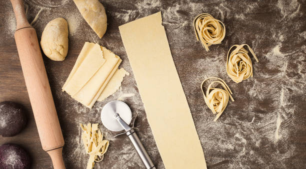 rohe tagliatelle-nest und teig auf küchentisch - italienische küchen dekor stock-fotos und bilder