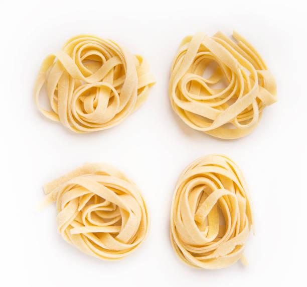 rohe tagliatelle nisten isoliert auf weiss - italienische küchen dekor stock-fotos und bilder