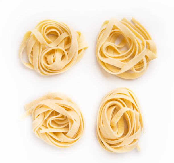 Raw tagliatelle nest isolated on white Raw tagliatelle nests isolated on white background. Traditional Italian pasta tagliatelle stock pictures, royalty-free photos & images