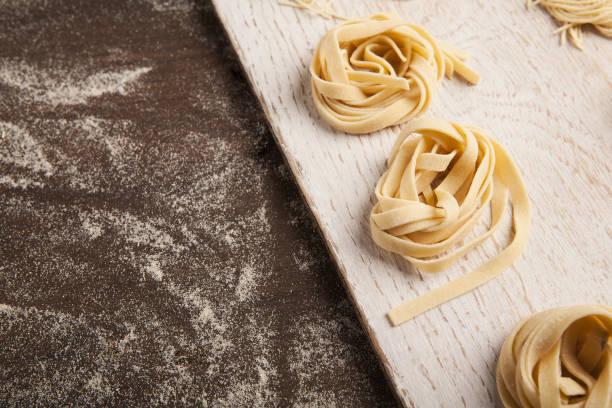 rohe tagliatelle-nest am küchentisch - italienische küchen dekor stock-fotos und bilder