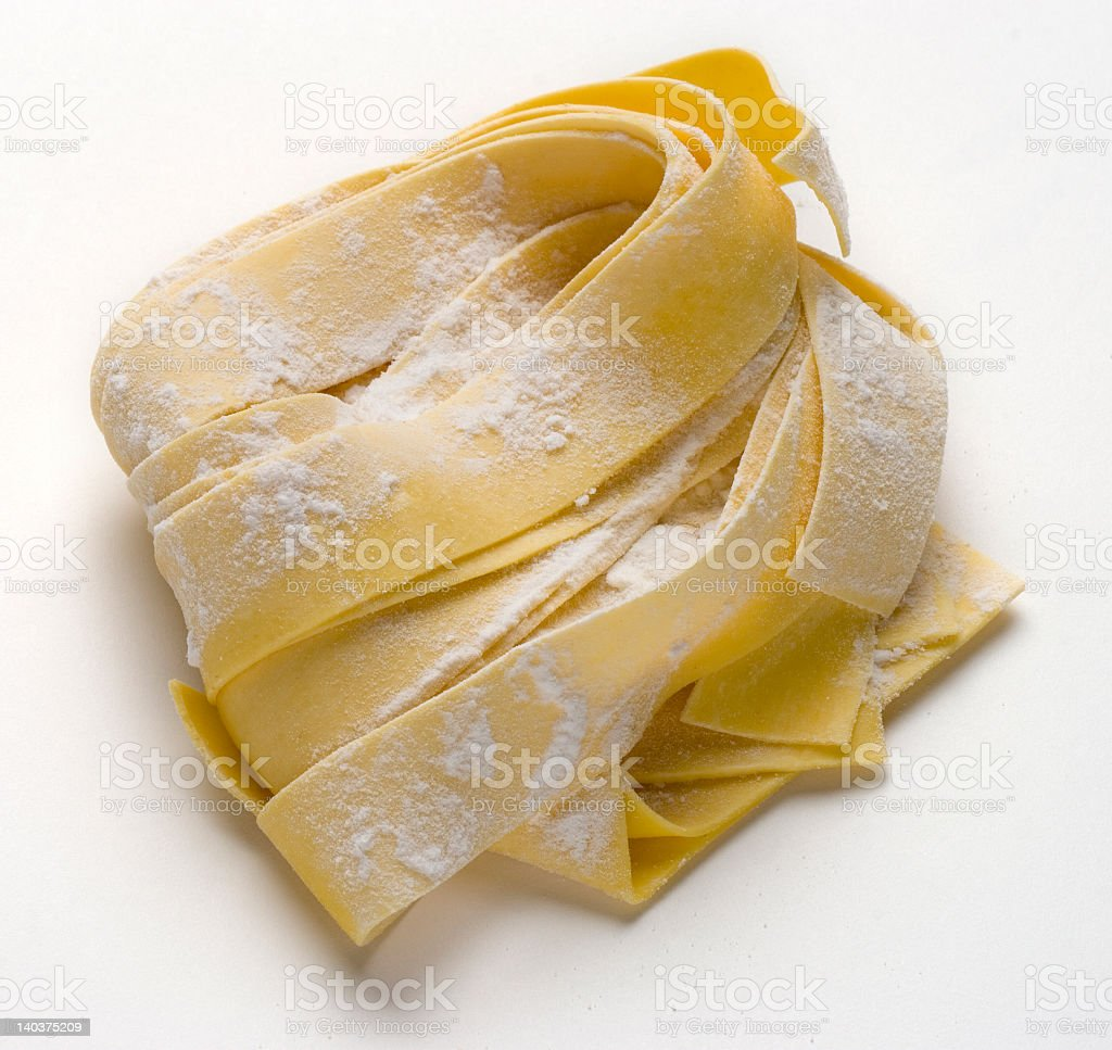 Raw tagliatelle pasta dusted in flour royalty-free stock photo