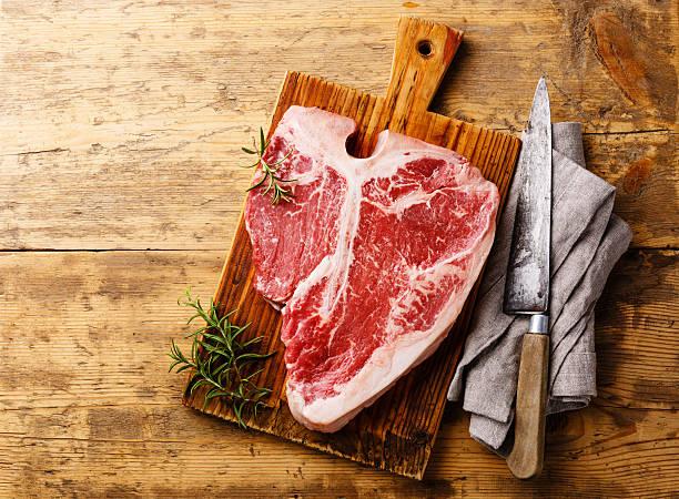 Raw T-bone steak and kitchen knife stock photo