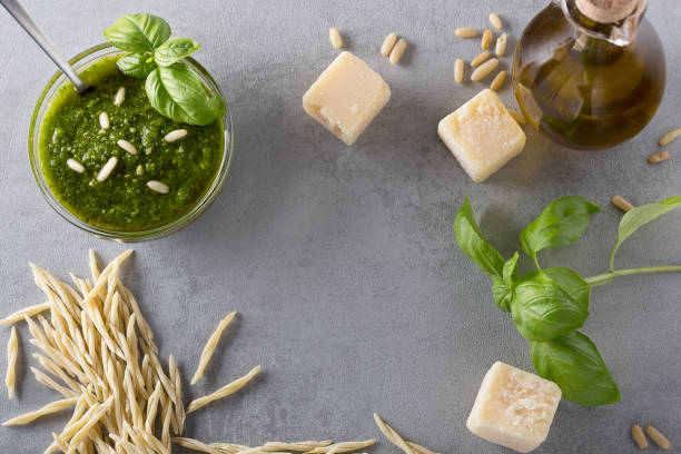 Raw trofie pasta and a glass bowl with pesto souace stock photo