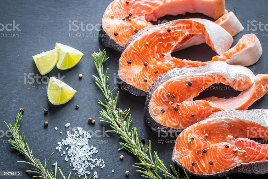 Raw trout steaks on the wooden board stock photo