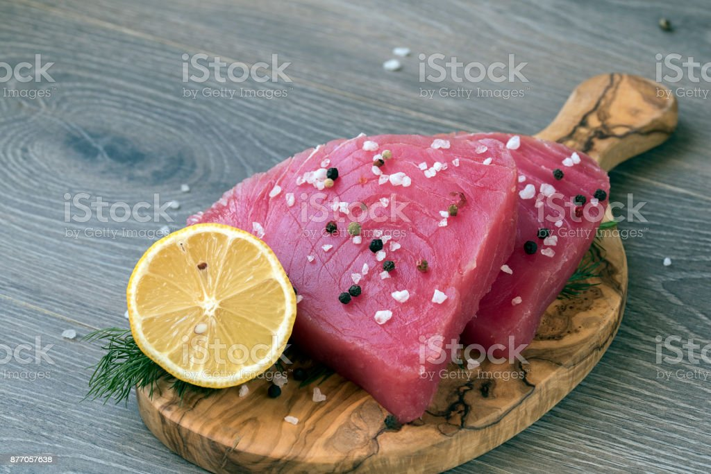 Raw tuna fillet with dill, lemon and peppers in olive cutting board stock photo