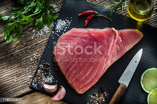 Raw food: top view of a fresh raw tuna steak on black slate board shot on rustic wooden table. Some ingredients for cooking tuna steaks like, olive oil, garlic, parsley, lime, salt and pepper are all around the cutting board with the fillet. Predominant colors are red, black and brown. Low key DSRL studio photo taken with Canon EOS 5D Mk II and Canon EF 100mm f/2.8L Macro IS USM.