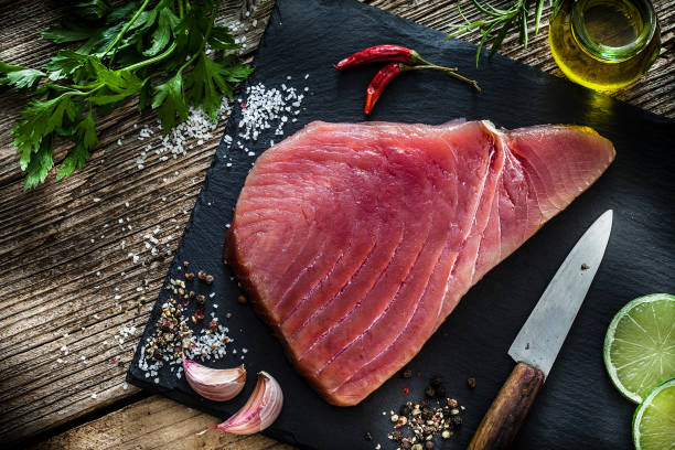 Raw tuna steak on rustic wooden table Raw food: top view of a fresh raw tuna steak on black slate board shot on rustic wooden table. Some ingredients for cooking tuna steaks like, olive oil, garlic, parsley, lime, salt and pepper are all around the cutting board with the fillet. Predominant colors are red, black and brown. Low key DSRL studio photo taken with Canon EOS 5D Mk II and Canon EF 100mm f/2.8L Macro IS USM. tuna seafood stock pictures, royalty-free photos & images
