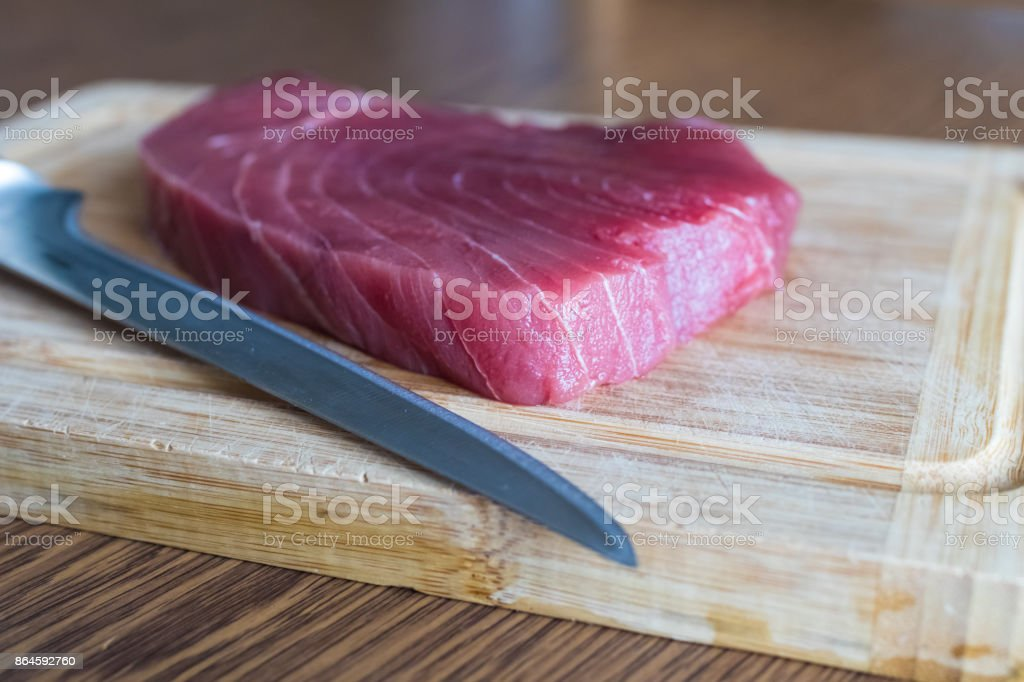 Raw tuna steak with knife ready to be sliced for sushi. Red tuna for tartarre stock photo