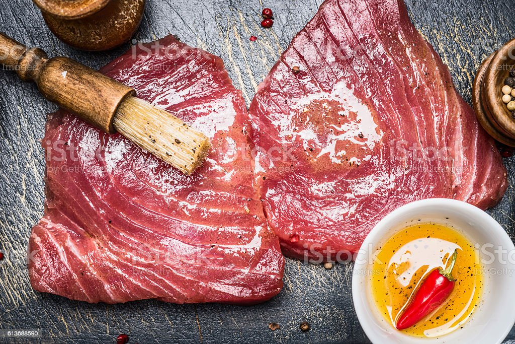 Raw tuna steaks marinating for cooking with brush and spices stock photo