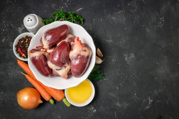 rohe putenherzen mit kräutern und gewürzen, gemüse karotten und zwiebeln auf dunklem hintergrund. zutaten für das kochen herzen von fal. gesunde seradienende nahrung. ansicht von oben - innereien stock-fotos und bilder
