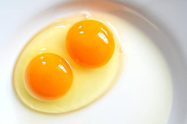raw two-yolk egg on the plate - yumurta sarısı stok fotoğraflar ve resimler