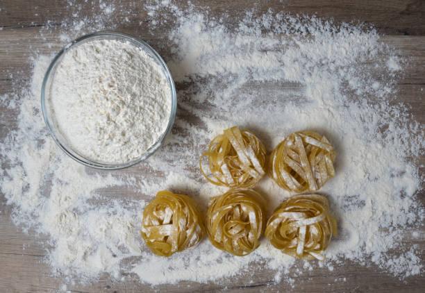 Roh ungekochte hausgemachte italienische Pasta Tagliatelle mit und Schalen mit weißem Mehl auf Holzhintergrund. – Foto