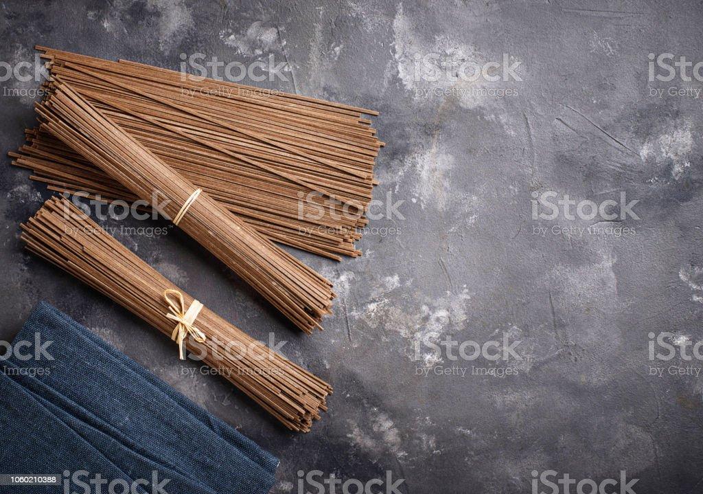 Raw uncooked Japanese soba noodles on grey bacground stock photo