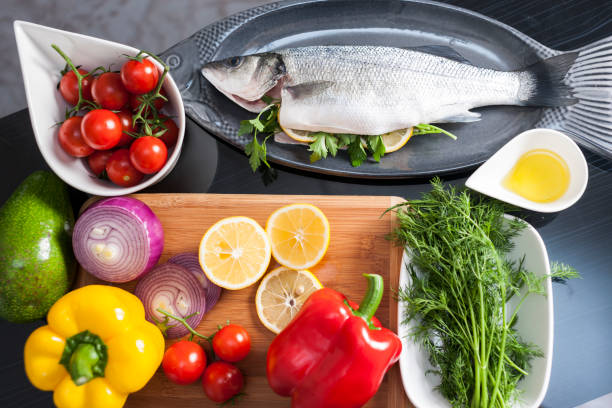 Raw uncooked sea bass with  lemon, olive oil, herbs and spices Raw uncooked sea bass with  lemon, olive oil, herbs and spices mediterranean sea stock pictures, royalty-free photos & images