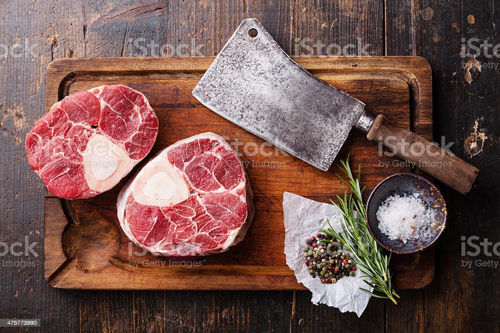 Raw veal shank for making OssoBuco and meat cleaver stock photo