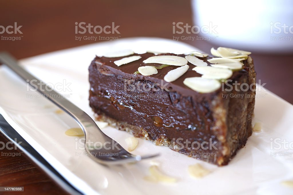 Raw vegan chocolate cake with ganache and flaked almonds royalty-free stock photo