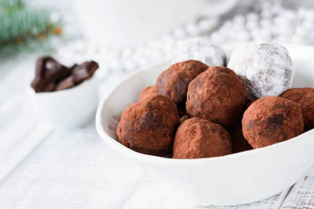 vegane schokolade trüffel mit datteln und rohe schokolade - low carb süßigkeiten stock-fotos und bilder