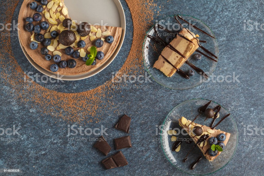 Raw vegan chocolate-caramel cheesecake with blueberries, raw candy balls and almonds. Healthy vegan food concept. Top view, dark background, flat lay stock photo