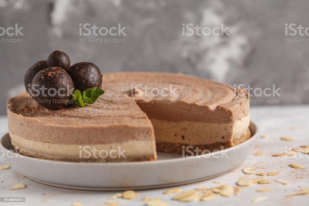 Raw vegan chocolate-caramel cheesecake with raw sweet balls. Healthy vegan food concept.  Light gray background. stock photo