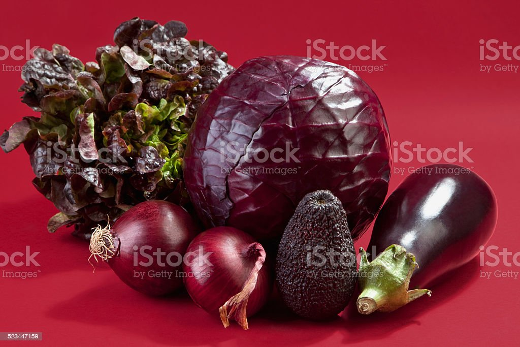 Raw vegetables against red background stock photo