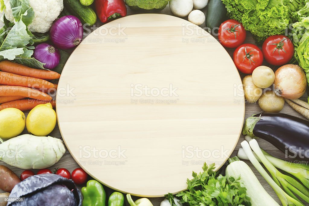 Raw vegetables and rounded plank stock photo