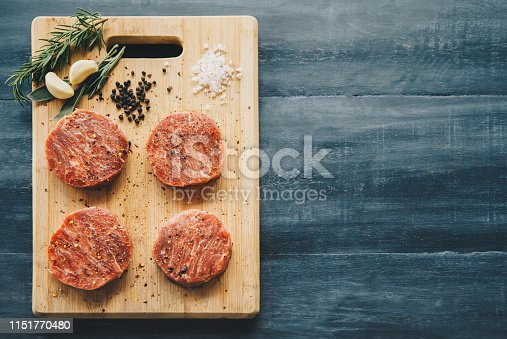 Raw wagyu beef steaks with seasoning on a wooden board