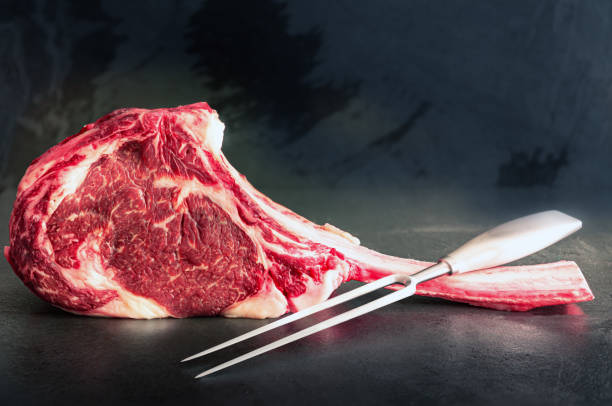 Raw Wagyu Tomahawk steak and a meat fork stock photo