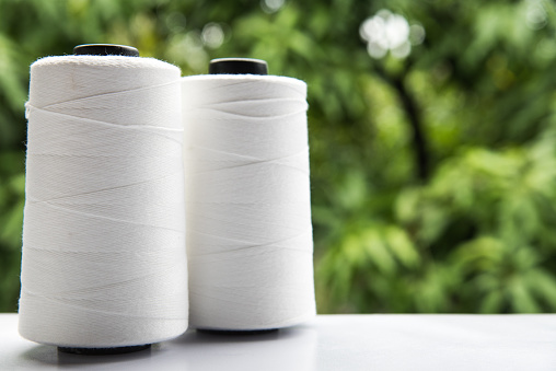 Raw White Polyester FDY Yarn spool with green blurred background