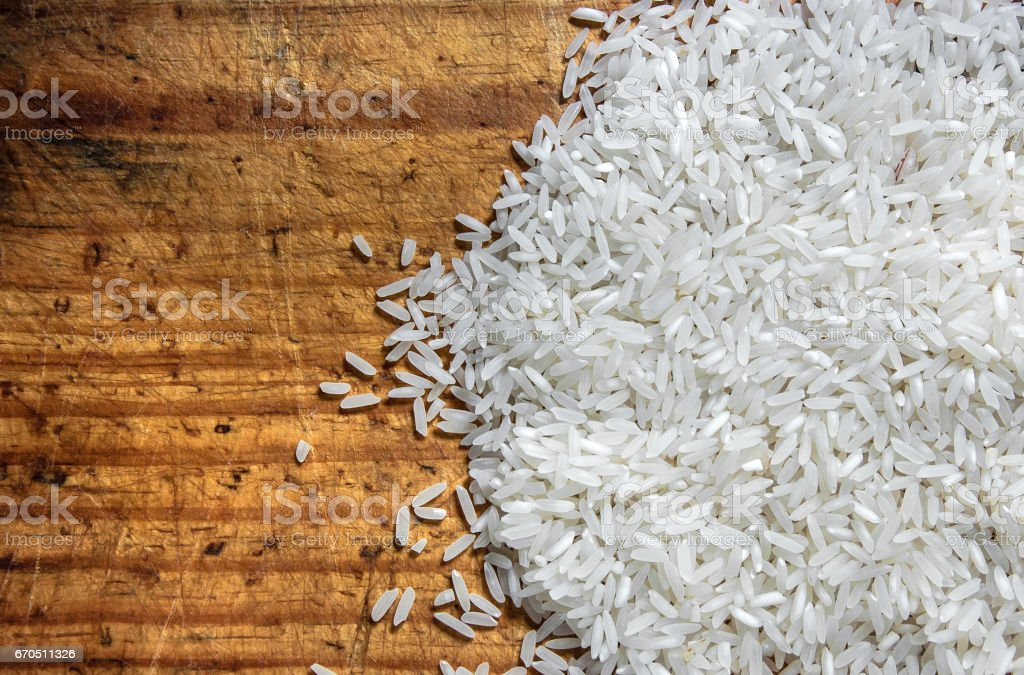 Raw White rice grain, over wooden cutting board, healthy eating, diet, cooking and foods concept stock photo