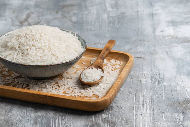 raw white rice in ceramic bowl with wooden spoon over gray background. wabi sabi style. copy space. horizontal. - dieta macrobiotica foto e immagini stock