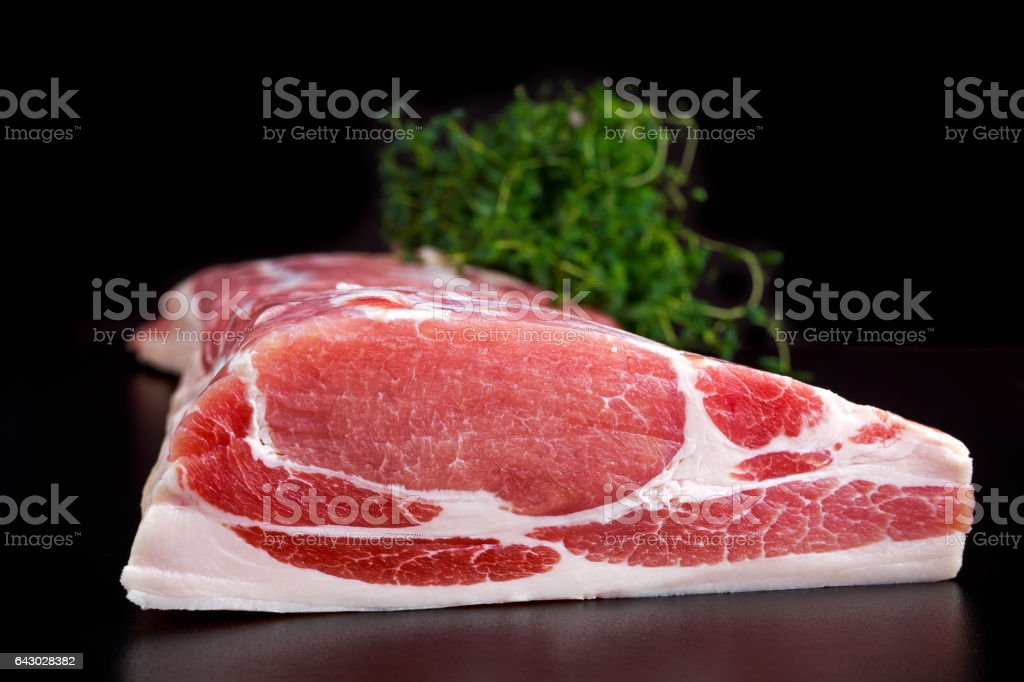 Raw whole back bacon loin with herb on black board background stock photo