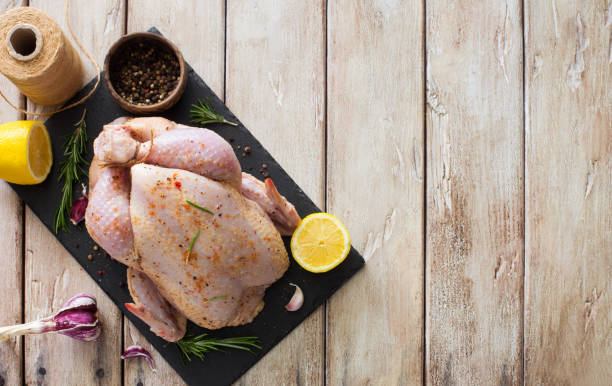 Raw whole chicken with lemon, rosemary and garlic stock photo